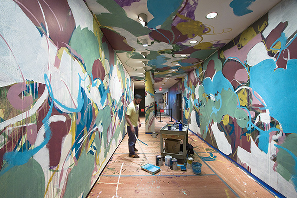 artist painting a hallway mural