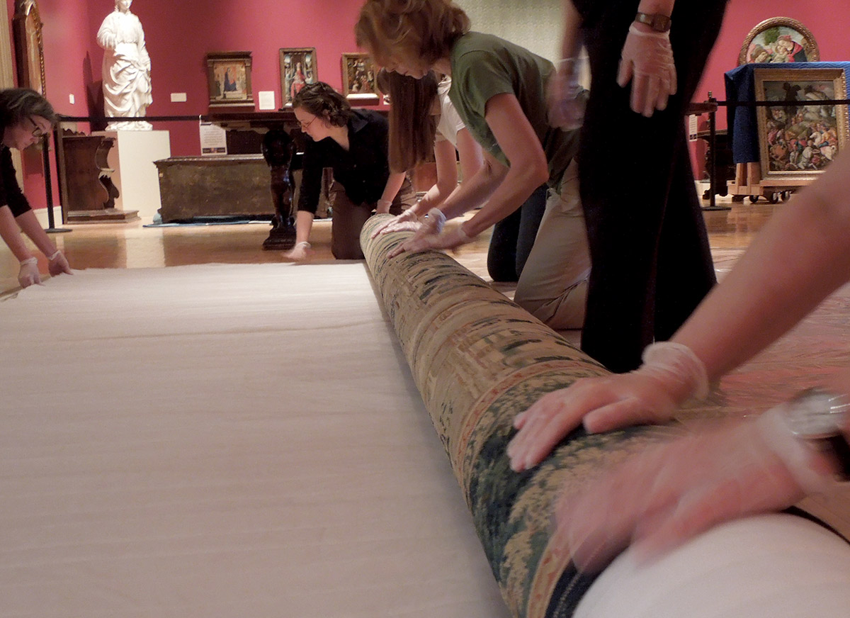 Curatorial staff unrolling a tapestry
