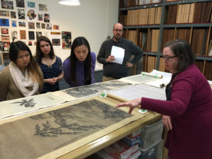 Curator Nancy Norwood displays scrolls to students in UR Professor Lihong Liu's class in Asian Art